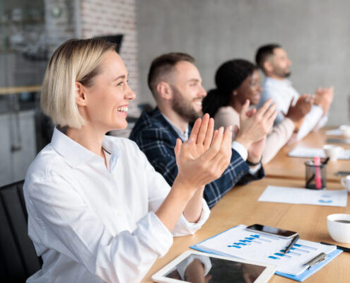 A cheerful business team claps while seated in a conference room.