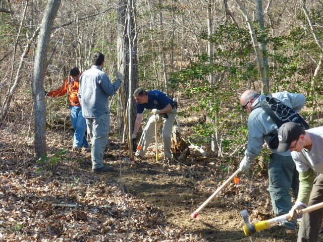 five men using tools to cut trail in the woods