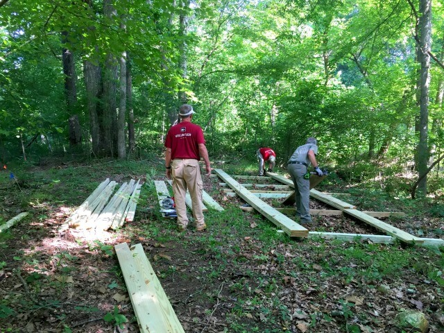photo of three men working on laying out a wooden bridge framework for a pedestrian footbridge on the HRT