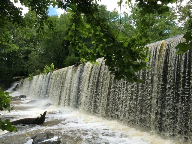 a view of the river pouring of the dam at Altamahaw with tree branches in the foreground