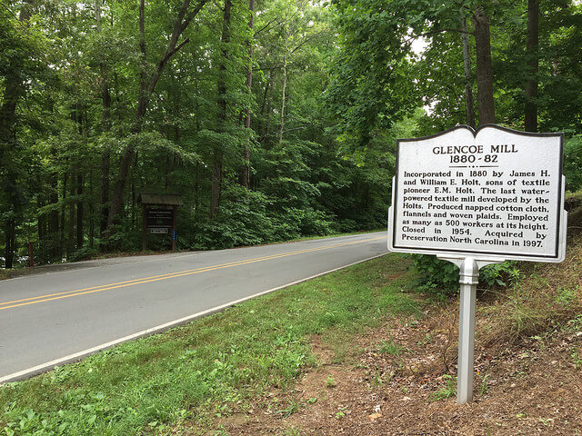 photo on the road of the Glencoe Mill historical marker with the Glencoe Mill Paddle Access entrance on the left