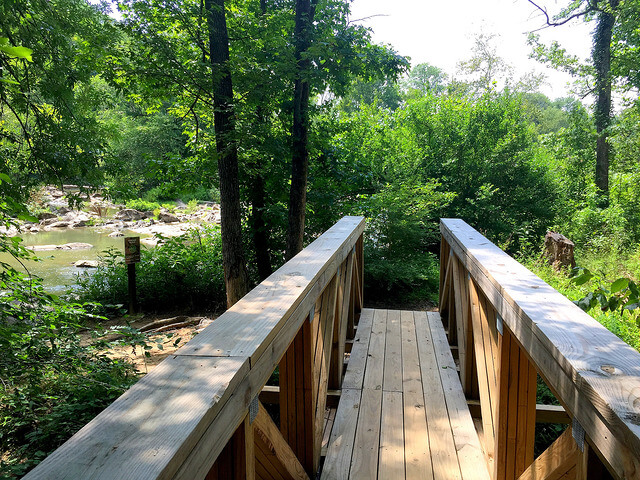 photo looking along a wooden pedestrian footbridge with vegetation in front and river to the left on a sunny day