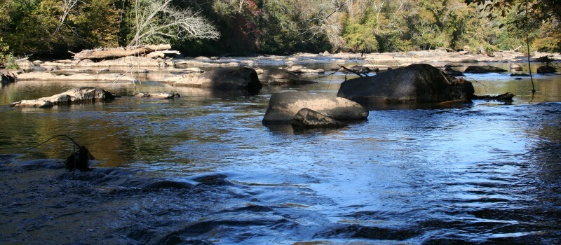 photo of river at Glencoe with water in foreground and rocks and trees in sunshine in background
