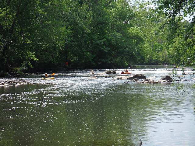 a photo of two kayakers in the Haw River with the Indian Valley dam behind them