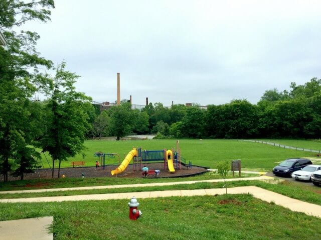 photo looking down on the playground at Red Slide Park with the field, river, and Granite Mill in the background and trees all around