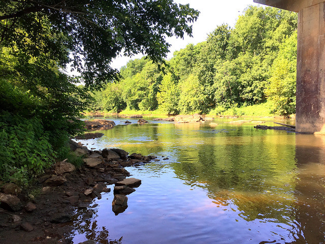 photo of the view downriver from Union Bridge Paddle Access, you can see the water with rocks on the shore and in the river and the concrete bridge piling on the right