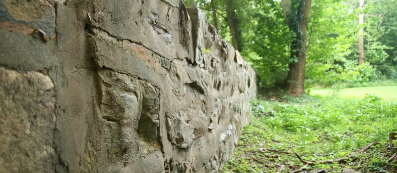 photo looking along a rockwall along the left edge with open field and trees to the right