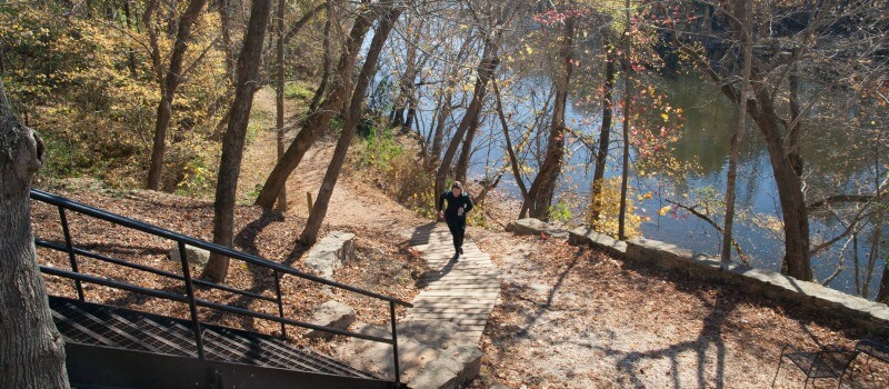 photo of a runner coming up the walkway from the trail to the steps in Saxapahaw with the river in the background