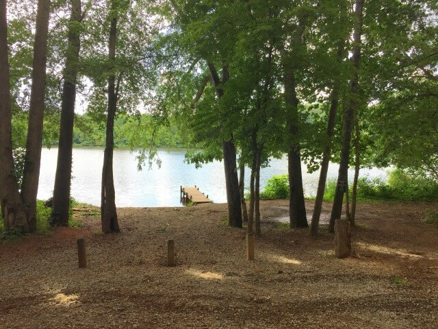 photo of the Saxapahaw Lake dock taken from the parking area looking out towards the river with trees in the foreground and trail entrance on the right