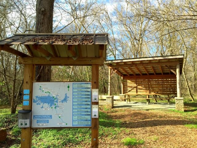 photo of welcome kiosk with river map in foreground and picnic shelter in background at Saxapahaw Mill Race Paddle Access