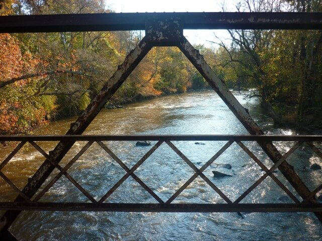 a bird's eye view of the Haw River seen through the metal railings of Goat Island Bridge with trees in Fall color in the background