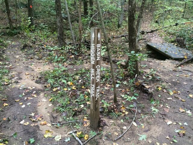 photo of a routed wooden trail marker pointing the way to the Hidden Hill Trail and Basin Creek Trail at a trail crossroads with a footbridge in the background and forest around it all