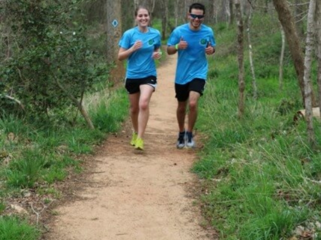 a male and female runner in blue event Tshirts running on the HRT during the Trailathlon with trees and grass on either side