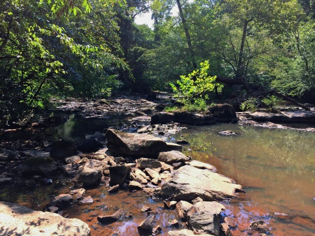 a photo of rocks and trees and the Haw River at Brooks Bridge Paddle Access