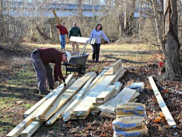 four volunteers carrying wooden boards to a pile of boards with a wheelbarrow and bags of concrete mix in the foreground