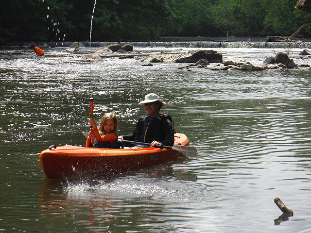 photo of dad and daughter in an orange kayak with dad holding the paddle and daughter playing with a watergun