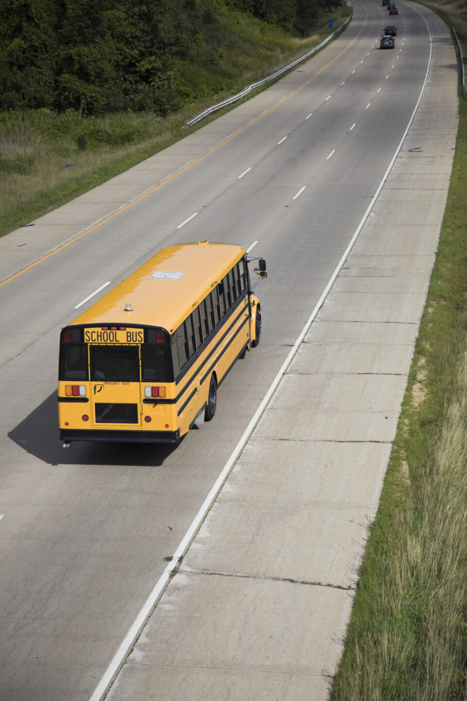 Yellow school bus travels along the road. Photo from envato elements