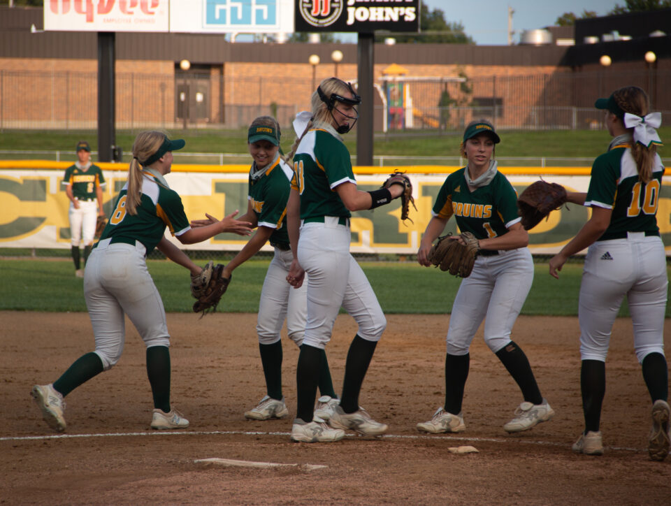 The team gathers at the pitching mound to exchange high fives. Pitcher Ella Schouten (12), struck out the first 6 batters she faced against Capital City on Sept. 14. Schouten had many more strikeouts as she continued to pitch the entire game. Photo by Emma Hake.