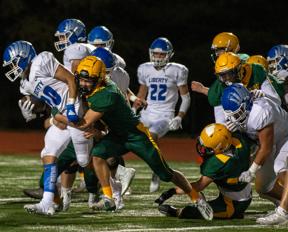 The football team attempts to stop LHS junior Wentric d. Williams Friday, Oct. 2. Photo by Ana Manzano.