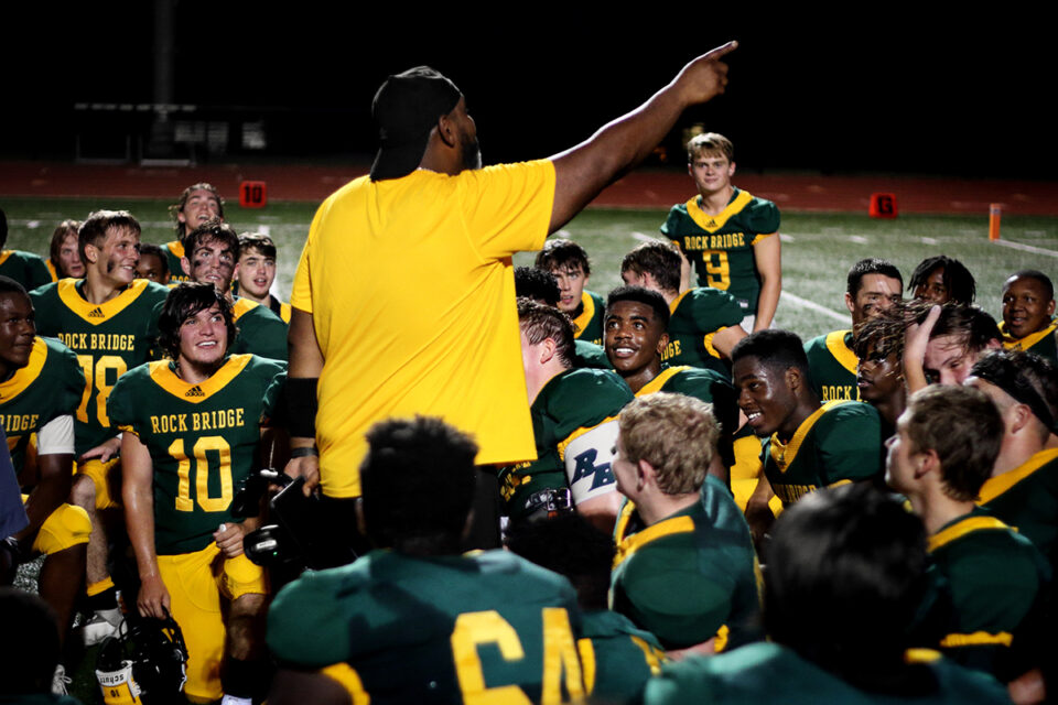 Senior Aiden Alvis looking up to coach Donnell Jones in a team huddle after the Bruins' 50-0 win. Photo by Desmond Kisida.