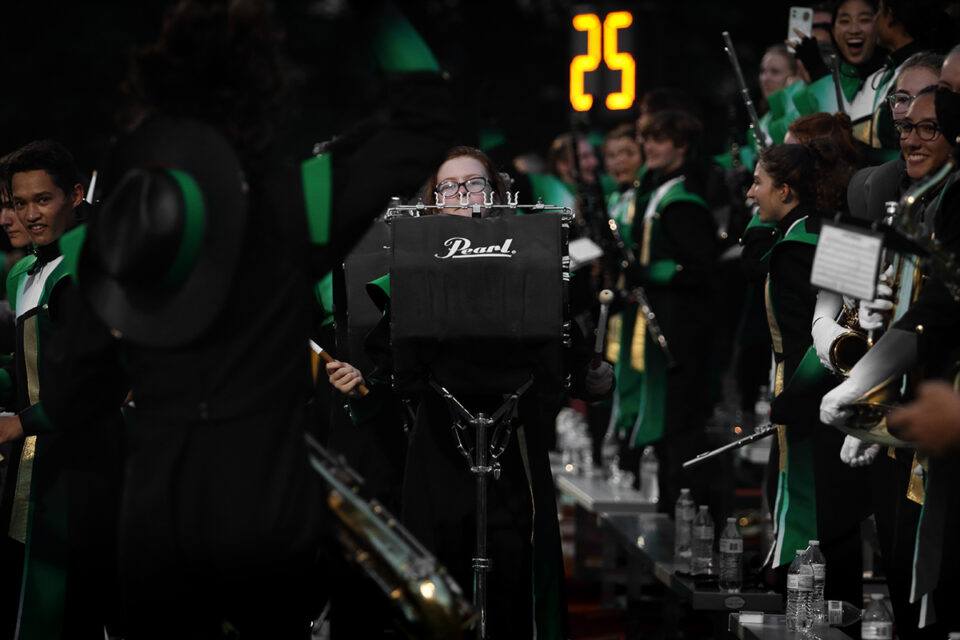 Sophomore Claire Calhoun playing the bass drum as senior Tivon Straub (foreground) jumps to the beat. Photo by Desmond Kisida.