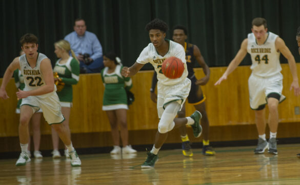 Being followed by his teammates, Senior Charles Wilson dribbles the ball to the the other side of the court at the varsity basketball game Tuesday, Dec. 7. Photo by Ana Manzano.