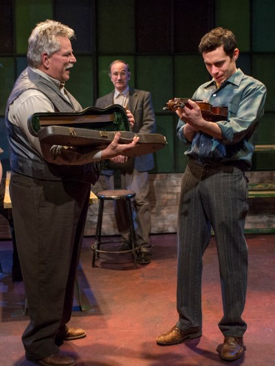 Joe (Nate Santana, right) has a mixed reaction to the gift of a violin from his father (Norm Woodel) as family friend Carp (Jerry Bloom) watches.  (Michael Brosilow)