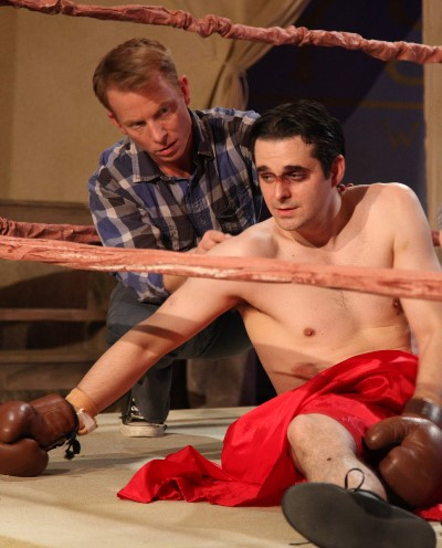 Down for the count, the carnival's headline boxer (Matthew Isler) gets a hand from Junior (Dan Waller). (Emily Schwartz)