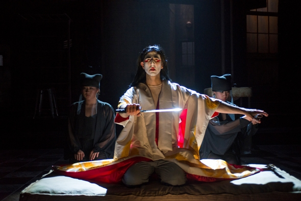 Sean Fortunato, as the disgraced Gallimard accused of espionage, puts on the ceremonial trappings in 'M.  Butterfly' by David Henry Hwang  at Court Theatre 2014 (Michael Brosilow)