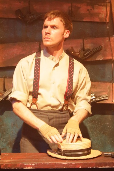 Jeff Meyer as the Proprietor of a shooting gallery on the weathered fairgrounds set designed by Zachary Gipson for Kokandy Productions at Theater Wit (Joshua Albanese)