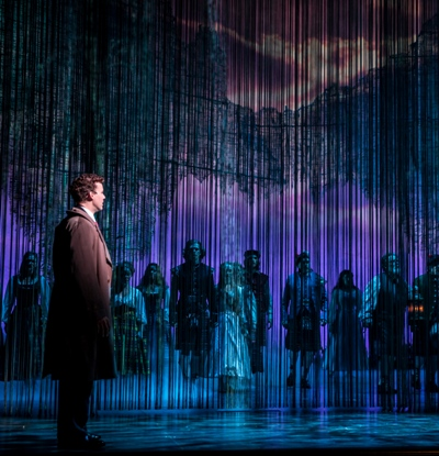 Tommy Albright (Kevin Earley) gazes upon the people of Brigadoon. Kevin Depinet's stage design depicts a town that lives for a day, then diesappears for 100 years. (Goodman Theatre, photo by Liz Lauren)