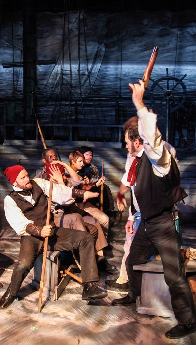 The ship's captain (Brad Woodard) fires a shot to quiet his frightened crew as they flee their sinking vessel. (Emily Schwartz)