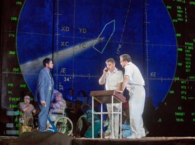 Aboard the Achille Lauro, under siege,  Metropolitan Opera 2014. Molqi (Sean Panikkar) stands guard over the first officer (Christopher Feigum) and the captain (Paulo Szot). Photo by Ken Howard