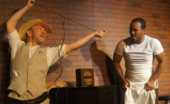 A Southern sheriff (Adam Bitterman) shows the black owner of a diner (Semaj Miller) how to use this fine radio he wants to trade for eight chicken dinners. (Tommy Lee Johnston)