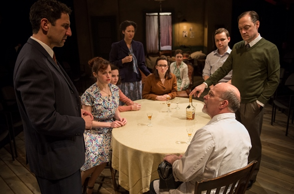 The dining table is the gathering place for Mr. van Daan (Lance Baker, standing far right) and other Jewish fugitives in 'The Diary of Anne Frank.' (Michael Brosilow)