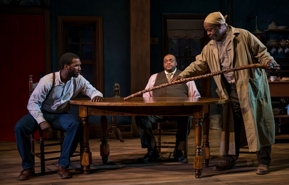 Solly Two Kings (Alfred H. Wilson) tells Citizen (Jerod Haynes) about his walking stick as Eli (A.C. Smith) looks on. (Michael Brosilow)