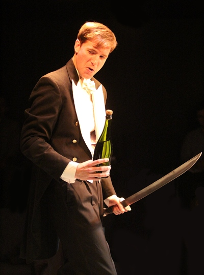 Champion of Riot Club tradition, Alistair (Michael Holding) prepares to open a bottle of Champagne. (Gregg Gilman)