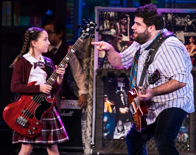 "Substitute teacher Dewey (Rob Colletti, right) may be a mess, but he knows that an electric bass is just what Katie (Theodora Silverman) needs. at the ""School of Rock."""