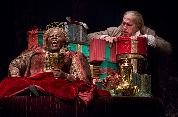 Ebeneezer Scrooge (Larry Yando) is amazed to find his bedroom occupied by the Ghost of Christmas Present (Lisa Gaye Dixon). (Liz Lauren)