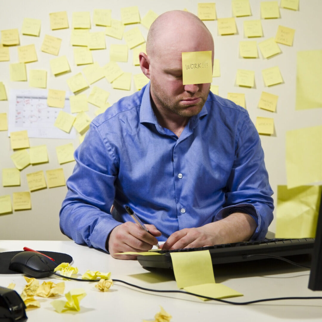 Office worker / businessman with too much work to do. Many notes in the background and one post-it at the forehead.