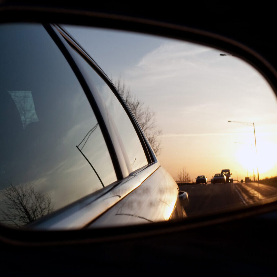 View of the sunset from the side view mirror of a car while driving down the road.  Shallow depth of field. Great image for illustrating blind spots.