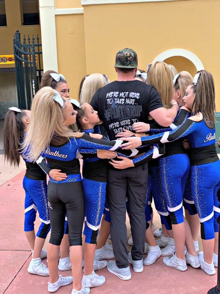 All the team hugging Terry and he is praying over them.