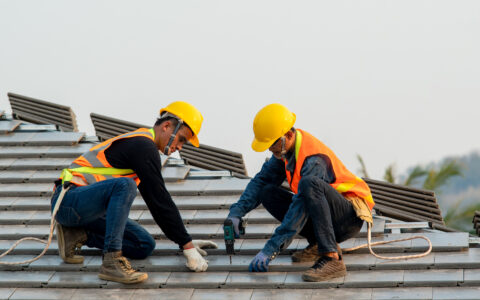 Construction worker wearing safety harness belt during working on roof structure of building on construction site,Roofer using air or pneumatic nail gun and installing concrete roof tile on top roof.