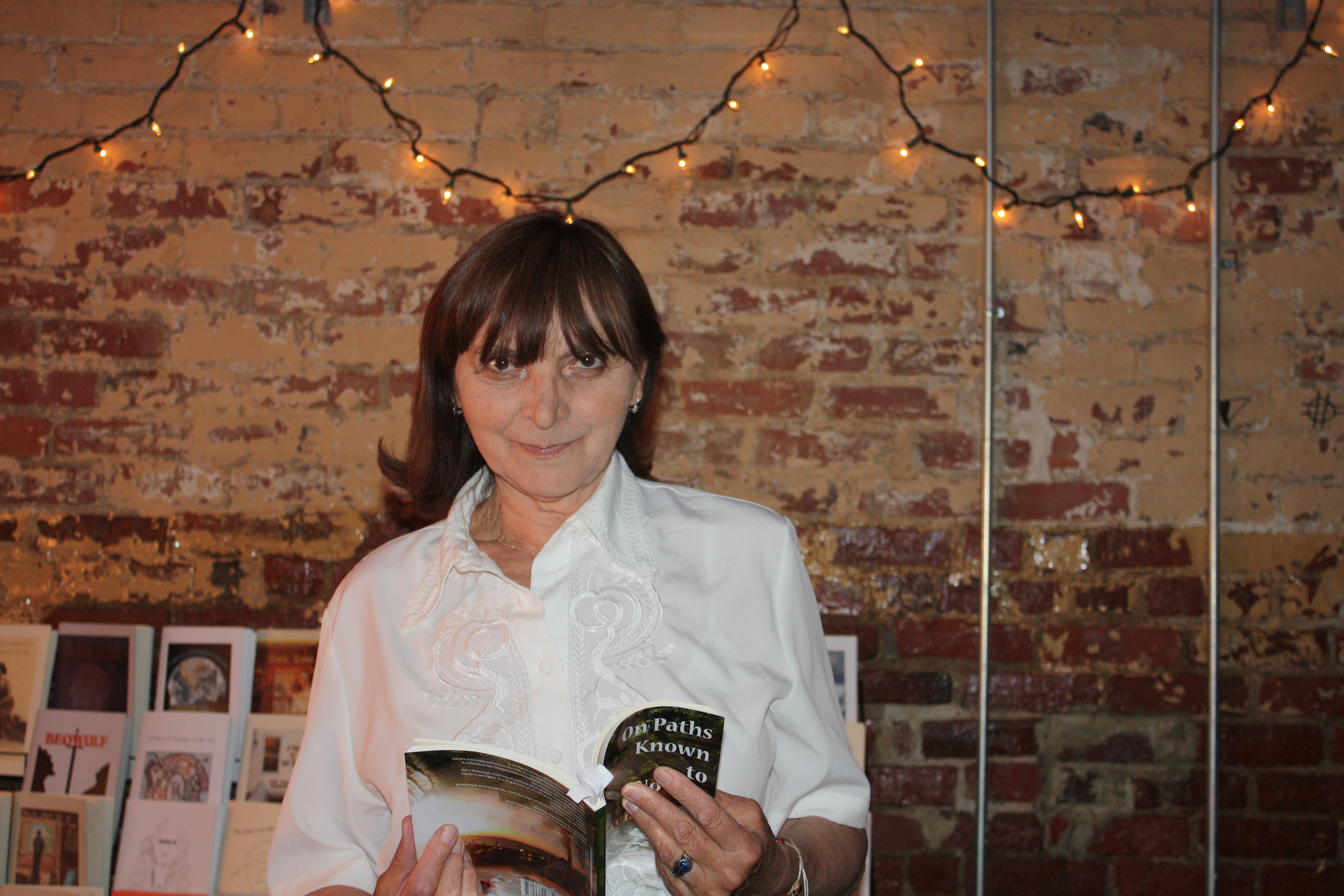 Flavia Cosma holding abook wearing a white button-up shirt