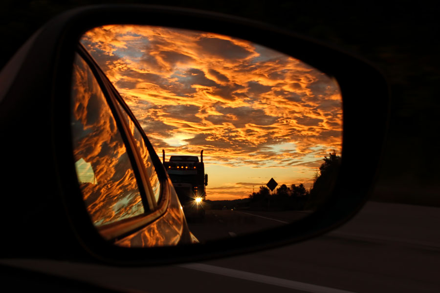 An 18-wheeler riding our bumper is illuminated by a brilliant reddish-orange sunset along Route 22 in Westmoreland County, PA. Captured in the passenger-side mirror at 65 mph.