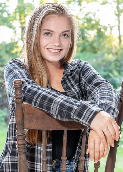 An old wooden chair serves as a prop in this casual senior portrait by State College portrait photographer Rusty Glessner