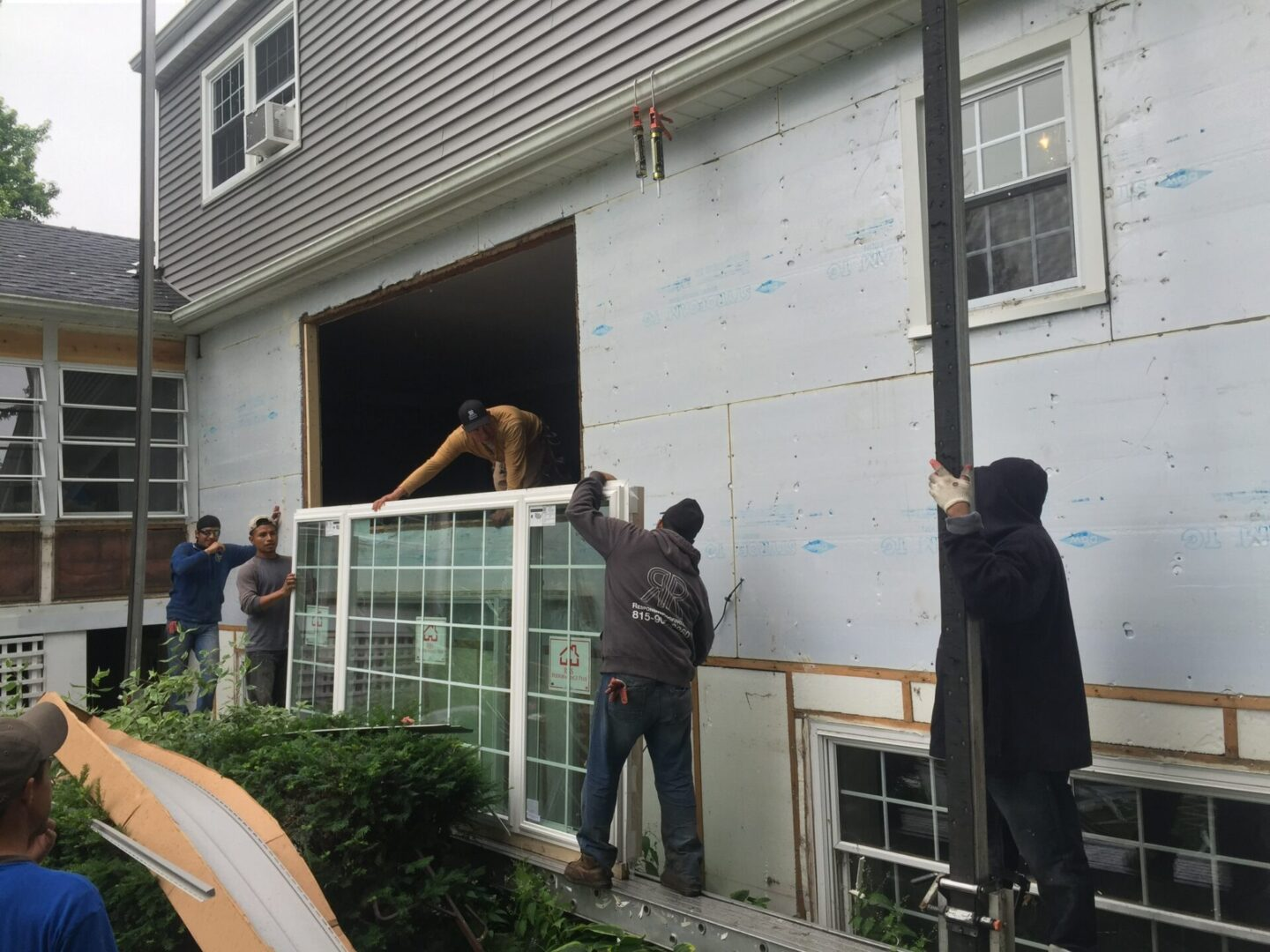 Personnel putting up a window
