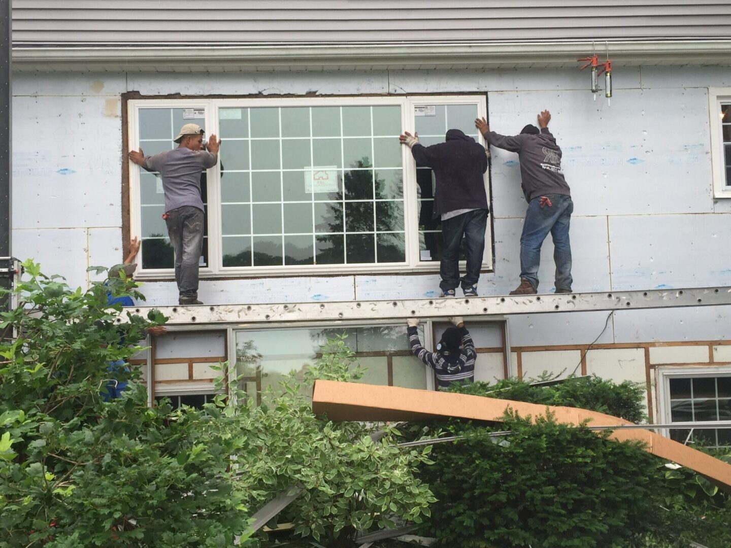 Men holding up a window