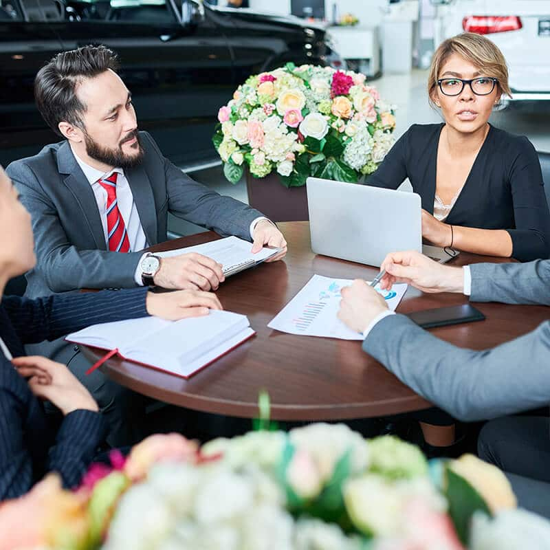 business people meeting at table in dealership