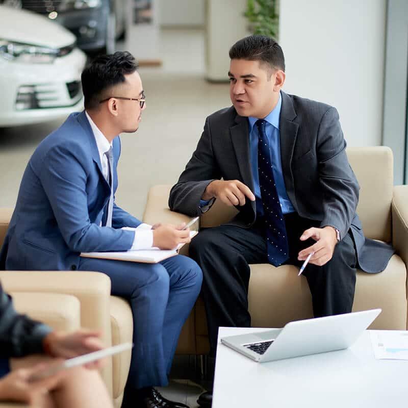 2 people sitting talking in dealership